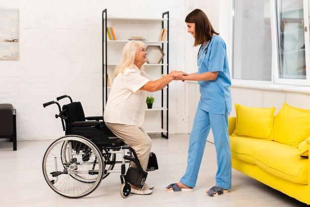 Afstandsschot verzorger die oude vrouw helpt