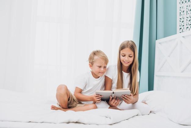 Afstandsschoten broers en zussen lezen samen een boek