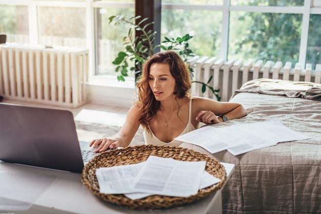 Afstandswerk. de vrouw werkt thuis, zit op de grond in de slaapkamer en gebruikt een laptop.