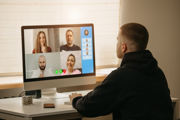 Afstandswerk. een achteraanzicht van een man tijdens een videogesprek met zijn collega's op de desktopcomputer. een kerel die een online briefing vanuit huis werkt.