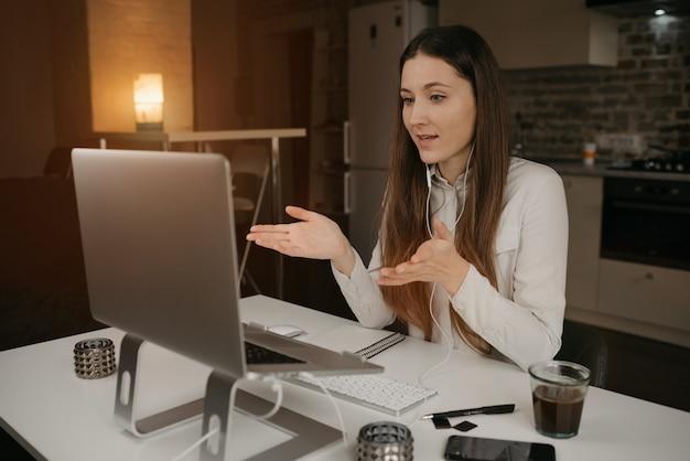 Afstandswerk. een blanke vrouw met koptelefoon werken op afstand online op haar laptop. een meisje dat actief zaken met haar collega's bespreekt via een videogesprek op haar gezellige thuiswerkplek.