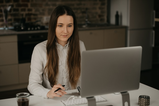 Afstandswerk. een kaukasische donkerbruine vrouw met hoofdtelefoons die ver aan haar laptop werkt. een dame in een wit overhemd die zaken doet op haar thuiswerkplek.