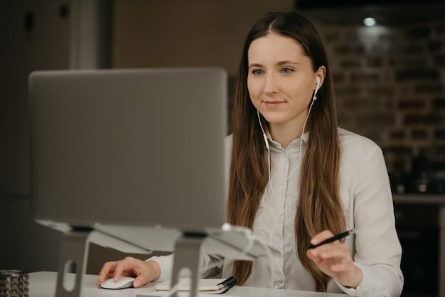 Afstandswerk. een kaukasische donkerbruine vrouw met hoofdtelefoons die ver aan haar laptop werkt. een onderneemster in een wit overhemd dat zaken doet op haar thuiswerkplaats.
