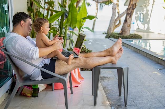 Afstandswerk. man met een peuter in zijn armen met een laptop bij het zwembad in een tropisch land