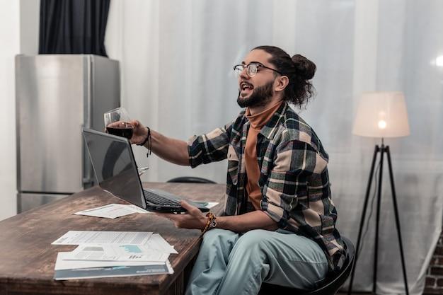 Afstandswerk. opgetogen positieve man die zijn laptop vasthoudt terwijl hij thuis wijn drinkt