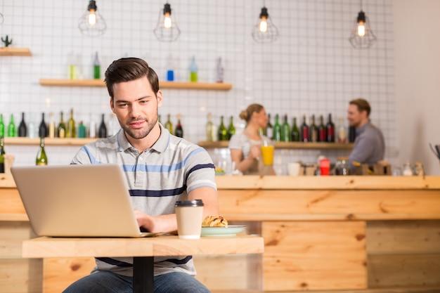 Afstandswerk. slimme aardige positieve man zit in het café en eten tijdens het werken op de laptop