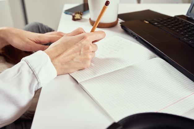 Afstandswerk. vrouw maakt aantekeningen in notitieblok en laptop gebruikt voor studie. afstandsonderwijs en e-learning concept