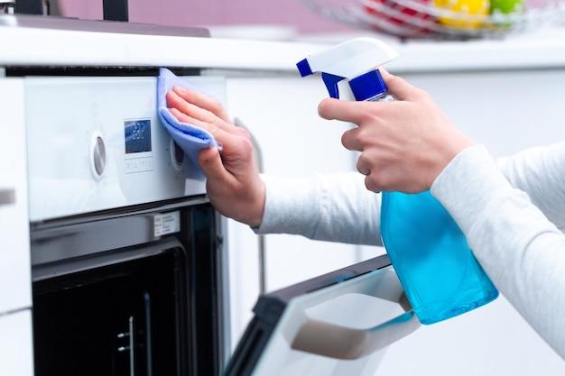 Afstoffen en polijsten gasfornuis met behulp van reinigingsproducten in de keuken thuis. huishouden, huishoudelijke taken. schoon huis, netheid