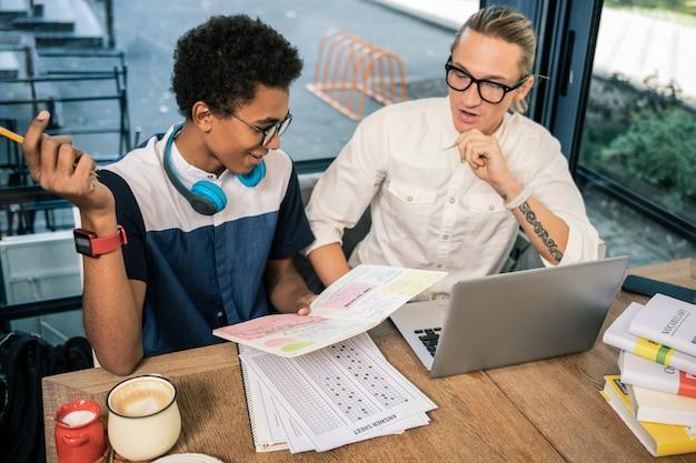 Afstudeer examens. opgetogen jongeman studeert met een tutor terwijl hij zich voorbereidt op een examen