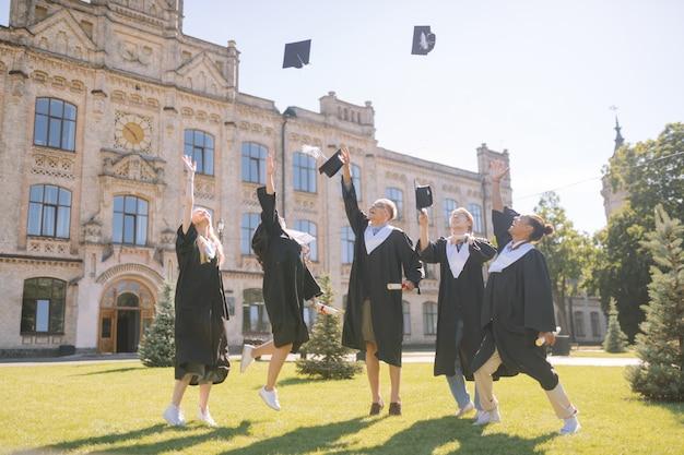 Afstudeerders gooien hun meestersmutsen op het universiteitsterrein