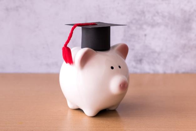 Afstudeerhoed op spaarvarken op tafel, geld besparen voor onderwijsconcept