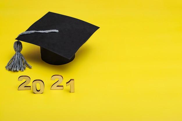 Afstuderen 2021. afgestudeerde pet op een gele achtergrond. afstudeersjabloon 2021