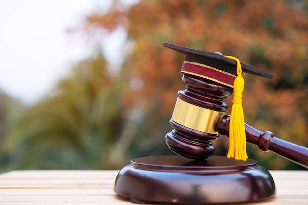 Afstuderen diploma hoed rechter hamer op schooladvocaat. concept van graduate studie internationaal in het buitenland