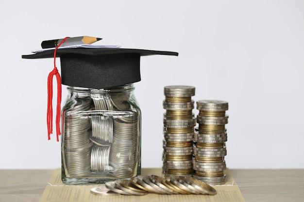 Afstuderen hoed op de glazen fles met stapel munten geld op wtite