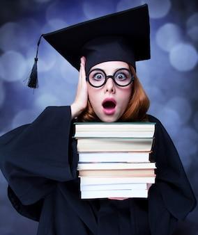 Afstuderen student meisje in een academische jurk met boeken