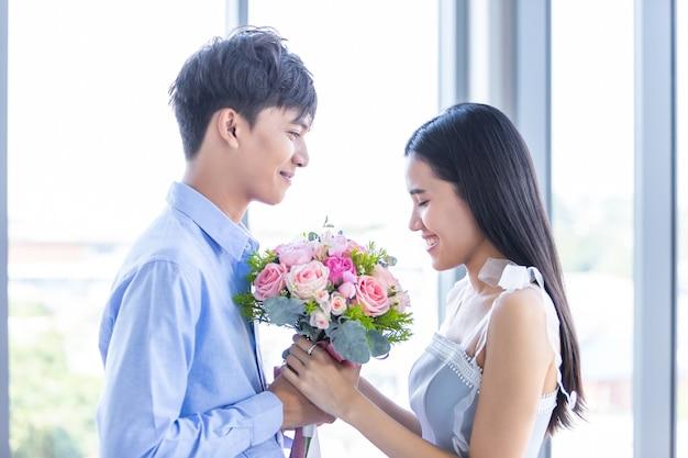 Aftelkalender voor valentijnsdag concept, aziatische jonge gelukkige zoete paar met boeket van rode en roze rozen na de lunch op de achtergrond van een restaurant, liefdesverhaal paar