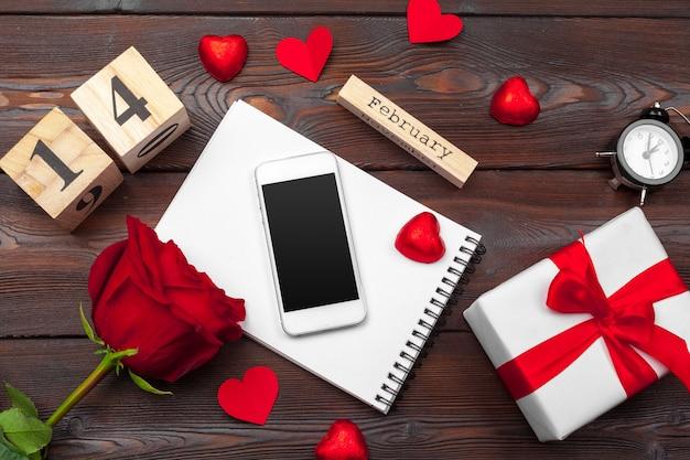 Aftelkalender voor valentijnsdag, lege lege laptop, geschenkdoos, bloemen op wit, bovenaanzicht, vrije ruimte voor tekst