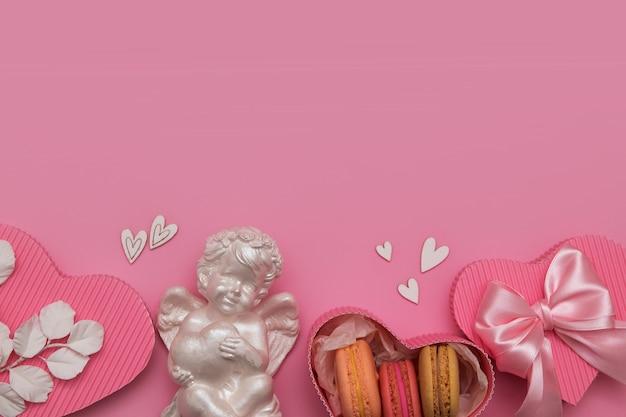 Aftelkalender voor valentijnsdag plat lag met geschenkdoos, macaron, boog, engel, harten op een roze achtergrond met kopie ruimte