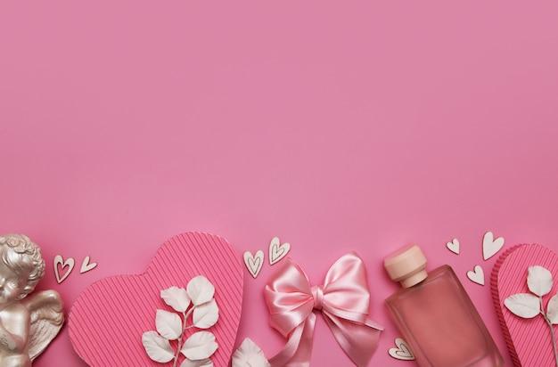 Aftelkalender voor valentijnsdag plat lag met geschenkdozen, boog, engel, harten op een roze achtergrond met kopie ruimte