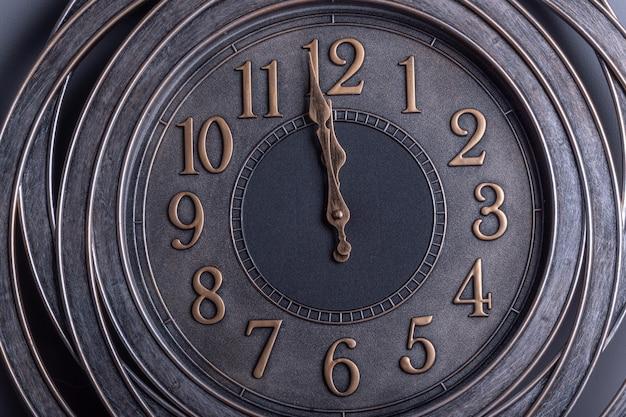 Aftellen tot middernacht.retro-stijl klok met goudachtige cijfers die één minuut voor middernacht aangeven.