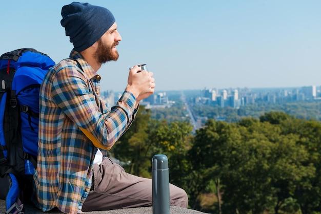 Afternoon tea op de top. knappe jongeman zit in de buurt van rugzak en kijkt weg terwijl hij drinkt