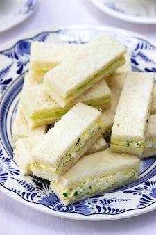 Afternoontea in de tuin, finger sandwiches met komkommer en eiersalade en thee op een lichtje.