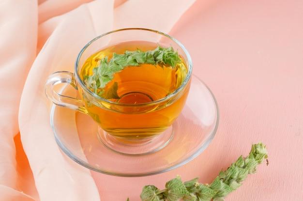 Aftreksel met kruiden in een glaskop op roze en textiel, hoge hoekmening.