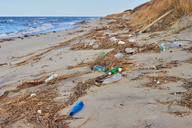 Afval en plastic flessen op het strand. het vuilnis wordt weggegooid door een storm