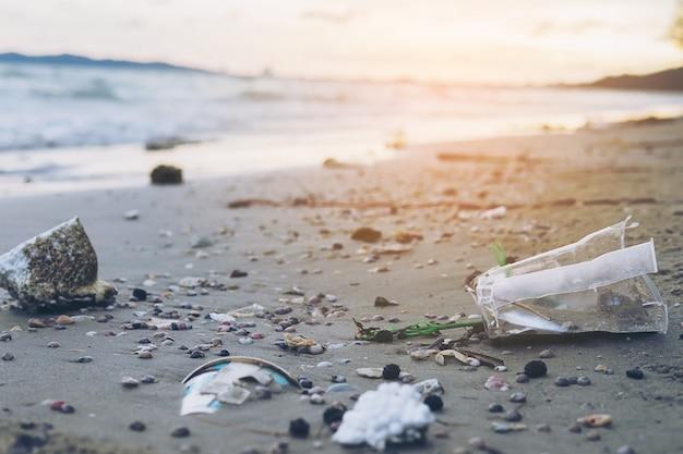 Afval op zandstrand dat milieuvervuilingsprobleem toont