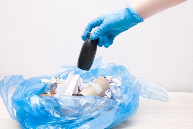 Afval sorteren concept, gooit vrouwelijke hand plastic verpakkingen in een zak