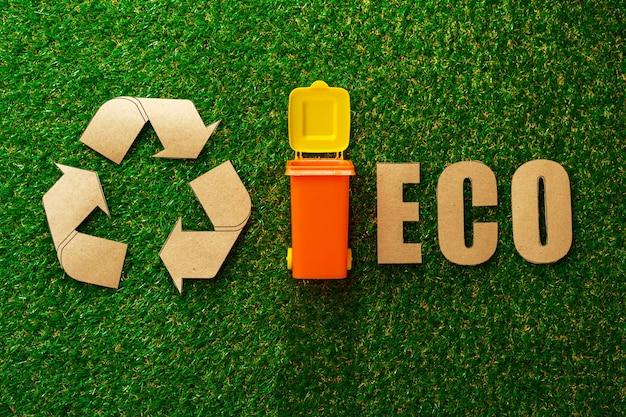 Afval sorteren concept met speelgoed afvalbak op papier achtergrond bovenaanzicht