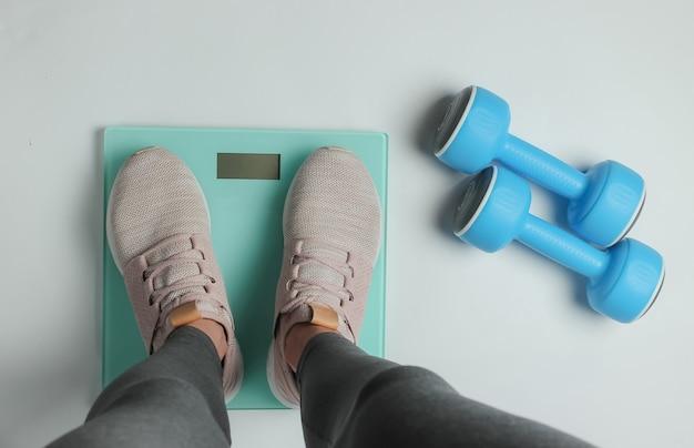 Afvallen, dieet, fitness concept. sport vrouw met beenkappen en sneakers meet haar gewicht met vloerweegschalen op een witte achtergrond. bovenaanzicht