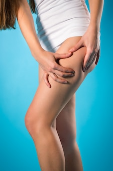 Afvallen, jonge vrouw die haar been controleert