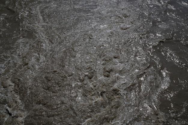 Afvalwater spatten. modder vuil water bruin water in de rivier, zand in het water in de lente