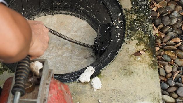 Afvoer reinigen. loodgieter die verstopte vetvanger met vijzelmachine herstelt. onderhoud riolering en vetafscheider door professionele loodgieter. met behulp van een vijzelslang om een afvoer te repareren en te ontstoppen.