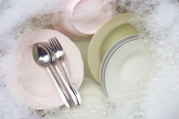 Afwassen, close-up van keukengerei doorweekt in aanrecht.