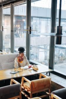 Afwerkingsproject. drukke slimme jonge freelancer die haar project in een restaurant afmaakt