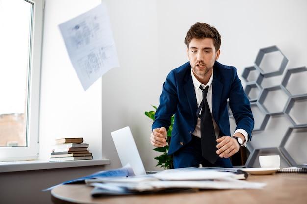 Afwezige jonge zakenman die in documenten, bureauachtergrond doorzoekt.