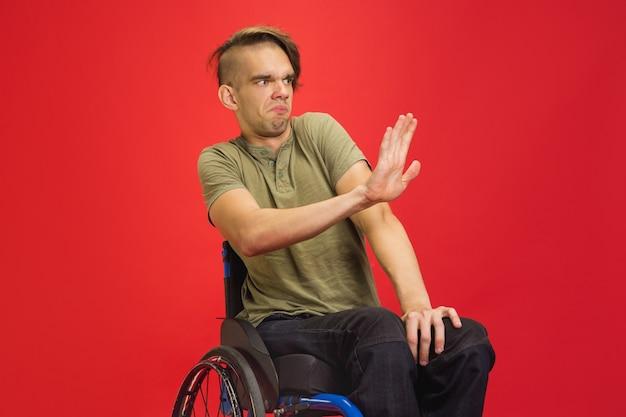 Afwijzen, stoppen. kaukasische jonge gehandicapte man portret op rode studio muur. kopieerruimte.