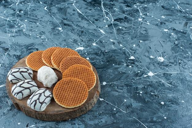 Afwisselend dessert op een bord, op de blauwe tafel.