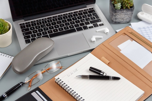 Agenda met handgeschreven to do list in de buurt van glazen en laptop op een grijze close-up geopend