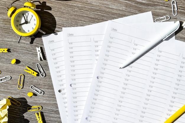 Agenda, uur per uur planner met wekker en kantoorbenodigdheden