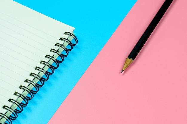 Agendaboek en een potlood op blauwe en roze achtergrond met exemplaarruimte. - bovenaanzicht.
