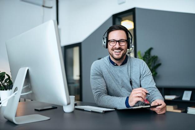 Agent die aantekeningen maakt tijdens een gesprek met de klant via een koptelefoon en microfoon in het klantenondersteuningscentrum.