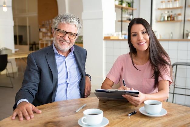 Agent en klant ontmoeten elkaar tijdens een kopje koffie bij co-working, zittend aan tafel, documenten vasthouden,