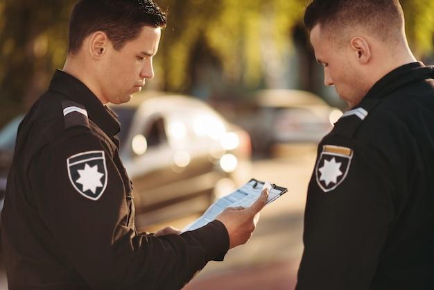 Agenten in uniform stoppen de auto op de weg