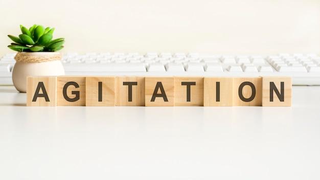 Agitatie woord gemaakt met houten blokken. vooraanzichtconcepten, groene plant in een bloemenvaas en wit toetsenbord op achtergrond