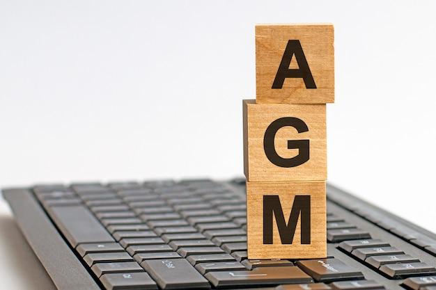 Agm jaarlijkse algemene vergadering acroniem op houten kubussen op grijs toetsenbord