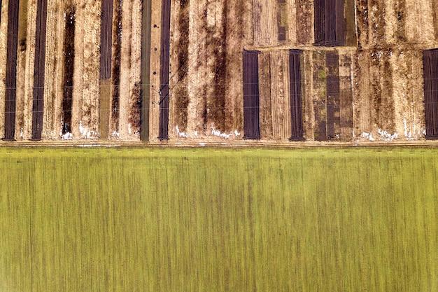 Agrarische landschap vanuit de lucht. rechte smalle grondweg tussen zonnig groen, droog en bruin omgeploegde akkers.