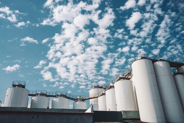 Agrarische silo's. opslag en drogen van granen, tarwe, maïs, soja, zonnebloem. industrieel gebouw buitenkant. grote metalen zilveren containers close-up.
